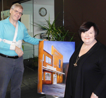Judie Fowler-Fletcher is pleased as punch with the commissioned architectural portrait of the newly renovated Carmichael headquarters.